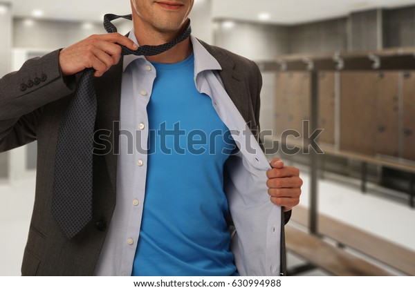 Young businessman taking off suit and tie and preparing for gym weight lifting workout after work. Sport healthy lifestyle, modern life rush, stress relief