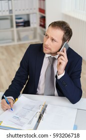 Young businessman talking by cell phone and looking away, sitting at office desk with pen in hand over documents in open folder
