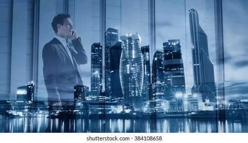 young businessman talking by phone, double exposure with modern blue city skyline