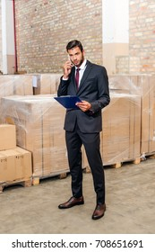 young businessman talking by phone at warehouse and holding clipboard