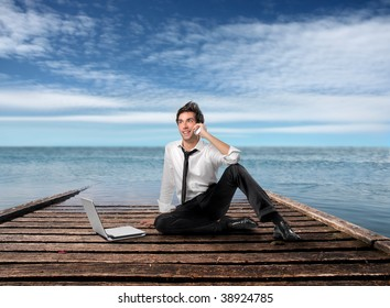 young businessman talking at mobile phone and using laptop on a wharf