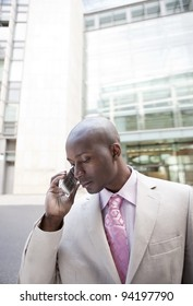 Young businessman talking on a cell phone standing by office building.