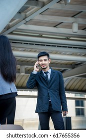 Young businessman talking on cellphone while standing in modern city