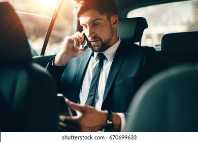 Young businessman talking on mobile phone and using tablet pc while sitting on back seat of a car. Caucasian male business executive travelling by a taxi and looking at digital tablet.