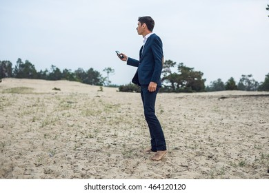 young businessman talking on the phone standing on the sand in the suit