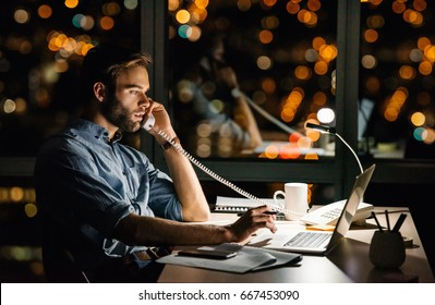 Young businessman talking on the phone and using a laptop at his office desk late t night in front of windows overlooking the city
