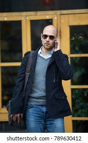 young businessman talking on the phone walking in the street