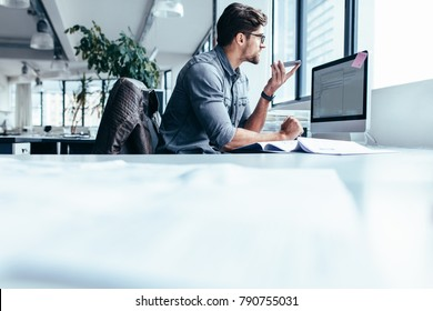 Young businessman talking on speaker phone. Young man sitting in office and working.