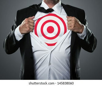 Young businessman tearing his shirt to show target symbol underneath