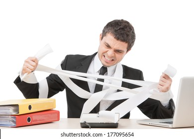 young businessman tearing paper apart. upset worker sitting at desk and calculating