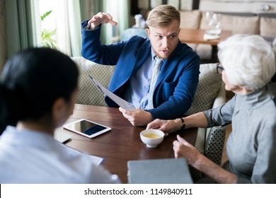 Young businessman telling future plans to senior leader while she drinking tea. They have meeting in a cafe