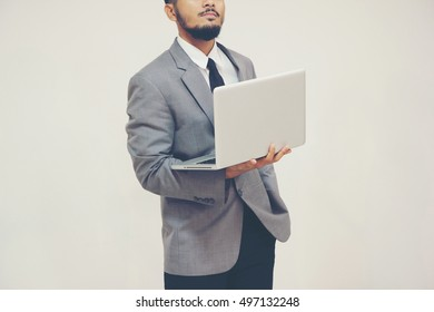 Young businessman thinking with laptop