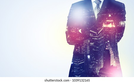 Young businessman thinking and standing with night skyscraper background