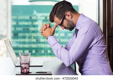 Young Businessman Thinking at Table