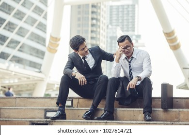 young businessman touching his forehead while his colleague consoling him