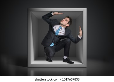 Young businessman trapped inside uncomfortable small box.