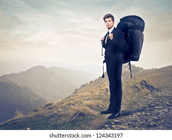 Young businessman with a travel backpack on a mountain
