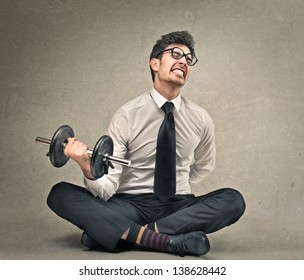 young businessman tries to lift a weight
