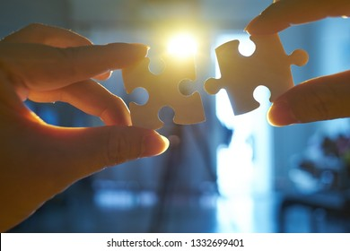 Young businessman trying to connect couple puzzle piece with sun flare and blur background,symbol of association and connection. business strategy.