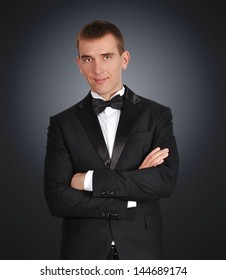 young businessman in tuxedo on black background
