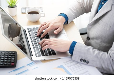 Young businessman is typing the business performance results on laptop computer keyboard. Online financial data analyzing concept.