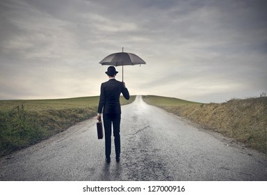 young businessman with umbrella on the road