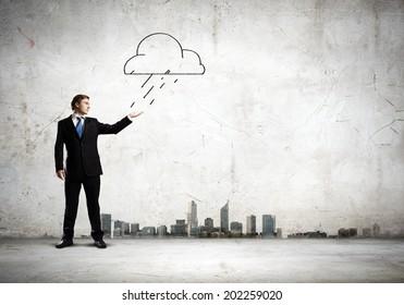 Young businessman under raining sky. Failure concept