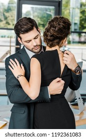 young businessman unzipping dress of seductive businesswoman at workplace in office