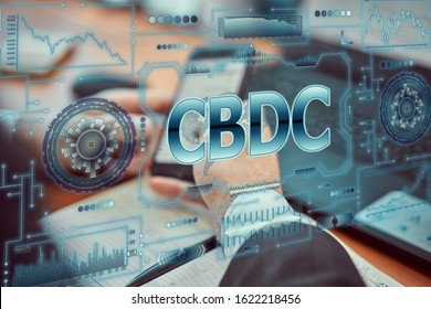 """A young businessman uses a futuristic smartphone with the latest holographic technology of augmented reality with the inscription """"CBDC"""". Central bank digital currency concept - Shutterstock ID 1622218456"""