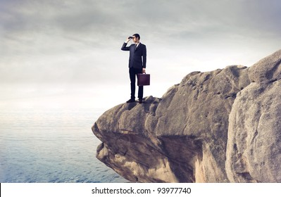 Young businessman using binoculars from a rock over the sea