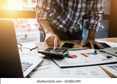 Young businessman using calculator and laptop computer is now finalizing sales this year to analyze sales growth by the world at work.