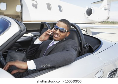 Young businessman using cell phone in convertible near private jet