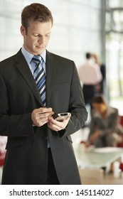 Young businessman using cellphone with stylus in office while colleagues working in background