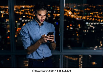 Young businessman using a cellphone while standing alone in an office late at night in front of windows overlooking the city
