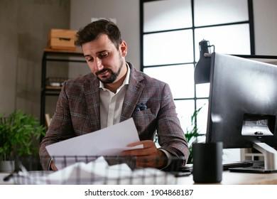 Junge Geschäftsleute, die in seinem Büro Computer benutzen. Schöner Mann, der an einem Projekt arbeitet.