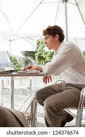 Young businessman using a laptop computer while sitting at a coffee shop terrace table under a parasol, outdoors.