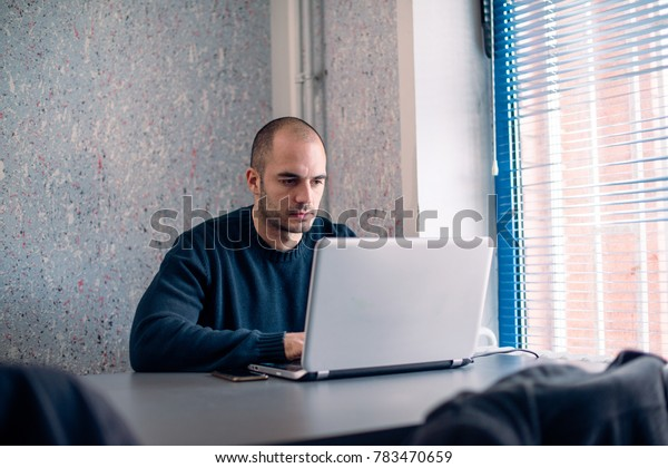 Young businessman using laptop in office, reading and typing.
