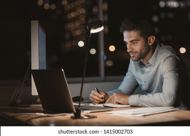 Young businessman using a laptop and writing notes while working overtime at his office desk late in the evening