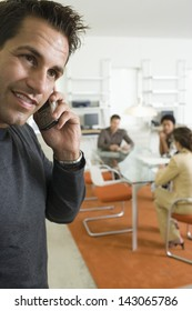 Young businessman using mobile phone with colleagues discussing in background