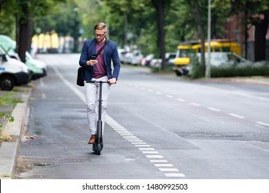 A Young Businessman Using Mobile Phone Riding An Electric Scooter On Road