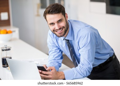 Young businessman using mobile phone while leaning on table at home