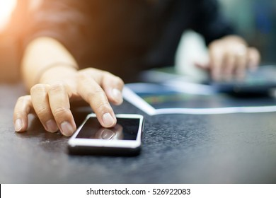 Young businessman using a phone and calculator in his office , and economic analysis