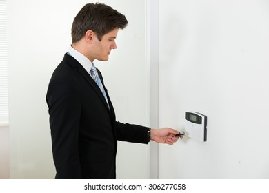 Young Businessman Using Remote Control For Operating Door Security System