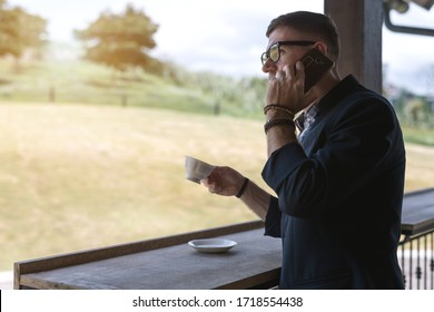 A young businessman using a smartphone and drinking coffee at home