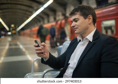 Young businessman using smartphone while waiting at the underground station. Blurred platform, train and people in background
