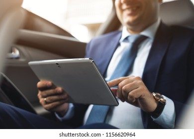 Young businessman using tablet pc while sitting on back seat of a car. Caucasian male business executive by a taxi and looking at digital tablet.