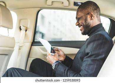 Young businessman using tablet while sitting in the backseat of a car.