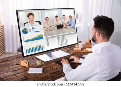 Young Businessman Video Conferencing With His Colleagues On Computer Over Wooden Desk