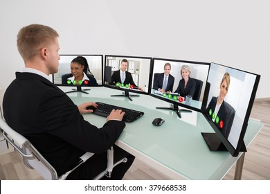 Young Businessman Video Conferencing On Desk With Multiple Computers