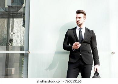 Young businessman waiting outside on the street, holding his smartphone